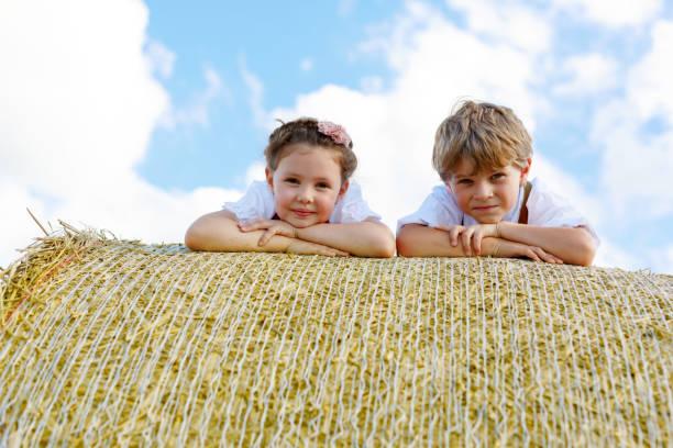 nahaufnahme von zwei kindern, die verlegung auf heuballen im weizenfeld. - sommerfest kindergarten stock-fotos und bilder