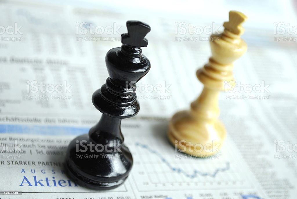 Close-up of two king chess pieces on newspaper stock photo