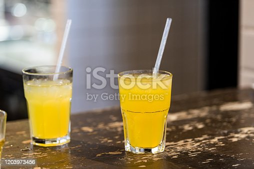 Closeup of two lemonade yellow juice drink cocktail glasses with plastic straws on table counter nobody