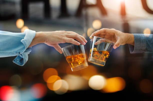 Nahaufnahme der beiden Männer anstoßen der Whisky trinken alkoholische Getränke zusammen, während am Tresen in der Kneipe nach der Arbeit auf farbigen Hintergrund – Foto