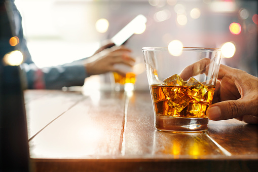 istock Close-up of two men clinking whiskey drink alcoholic beverage at bar counter in the pub background. 1051670730