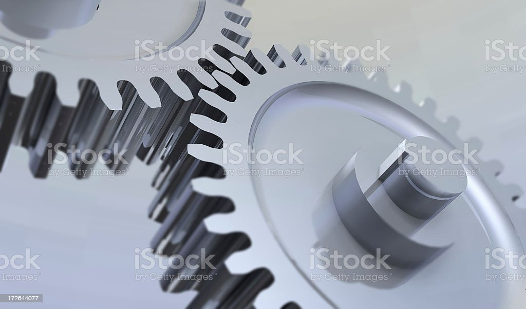 Close-up of two metal gears over silver background royalty-free stock photo
