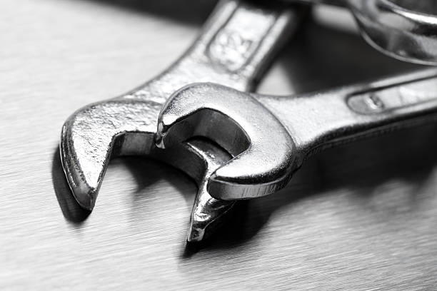 Close-up of two metal wrenches lying on a metal table stock photo