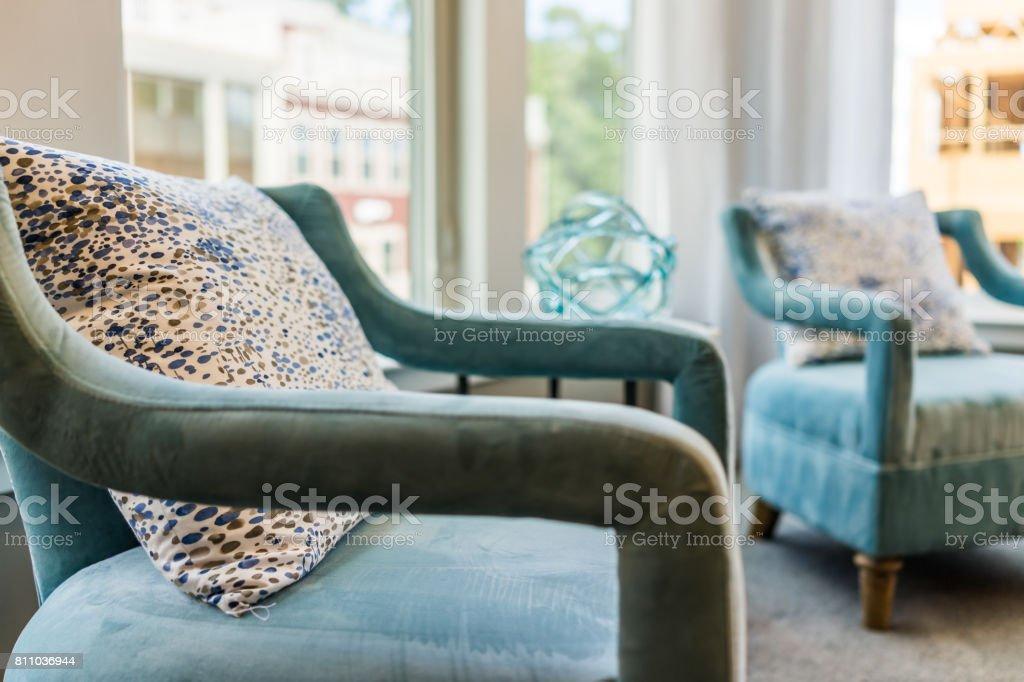Closeup de duas cadeiras de sofá azul moderno novo por janelas com luz natural e almofadas foto royalty-free