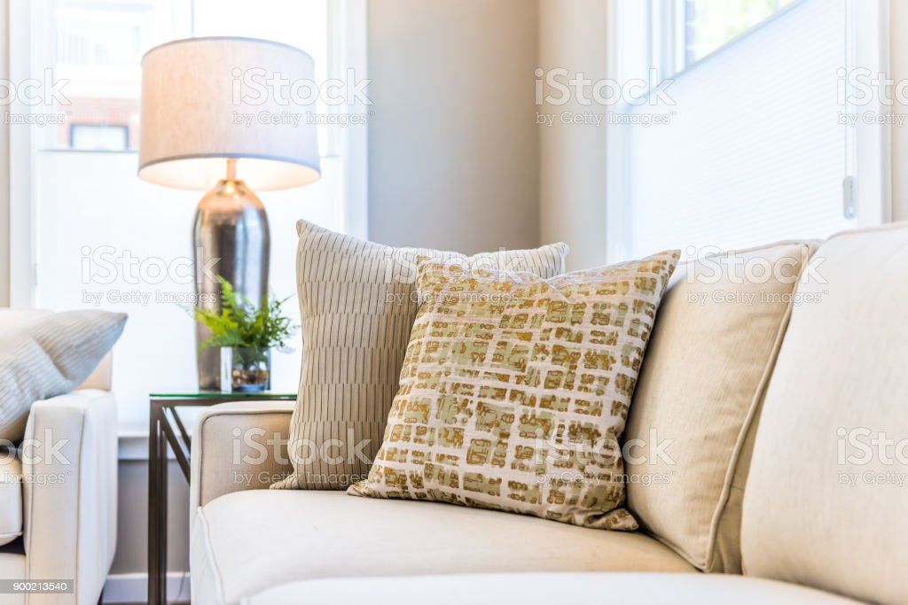 Closeup of two pillows on couch or sofa by bright window in modern apartment, house or home with staging of large beige, neutral white colors, lamp stock photo