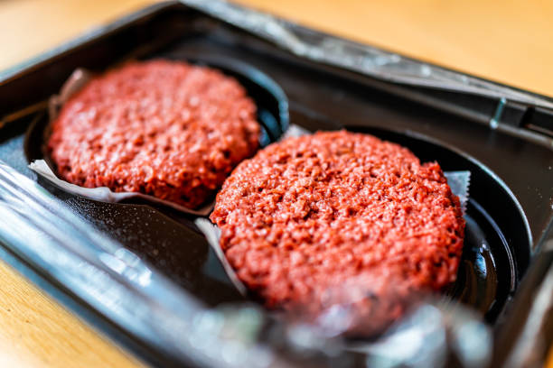 Closeup of two raw uncooked red vegan meat burger patties in plastic packaging Closeup of two raw uncooked red vegan meat burger patties in plastic packaging vegetarian stock pictures, royalty-free photos & images