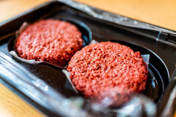 close-up van twee rauwe ongekookte rode vegan vlees hamburger pastei in plastic verpakkingen - vleesvervanger stockfoto's en -beelden