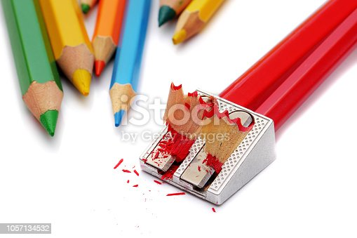 closeup of two red pencils in dual aluminum pencil sharpener isolated on white background