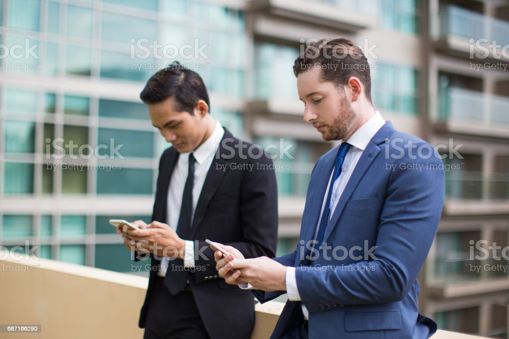 Nahaufnahme von zwei schweren Kollegen SMS im freien Lizenzfreies stock-foto
