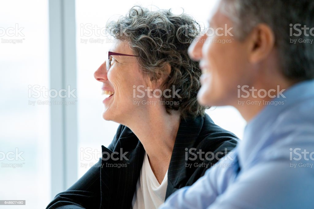 Closeup of Two Smiling Coworkers at Meeting stock photo