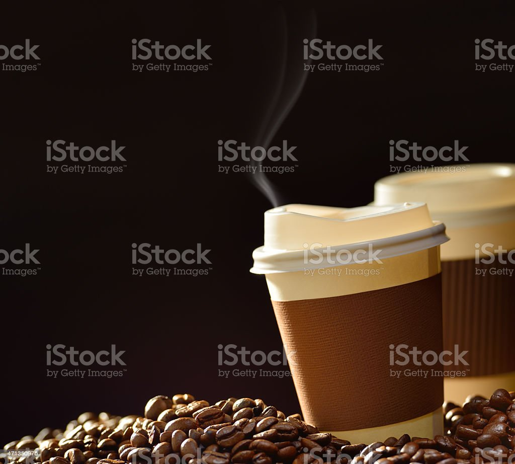 A close-up of two steaming cups of coffee with coffee beans stock photo