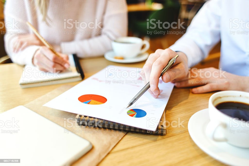 Close-up of two unrecognizable business people exploring charts in financial report while sitting at cafe table and having coffee royalty-free stock photo