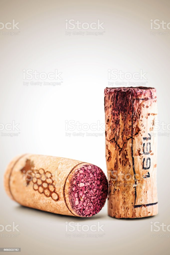Close-up of two wine corks with one cracked old from 1991 and one new bottle stopper in studio on bright background - Photo