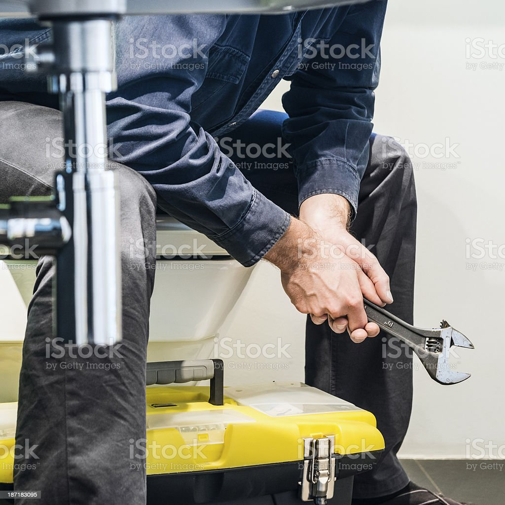Close-up of unemployed plumber sitting and thinking on toilet bowl royalty-free stock photo