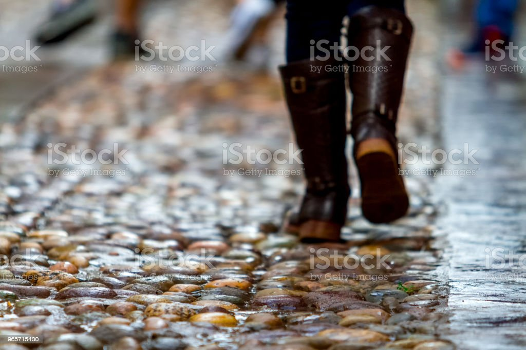Close-up of unfocused woman's feet on a cobbled street - Royalty-free Adult Stock Photo