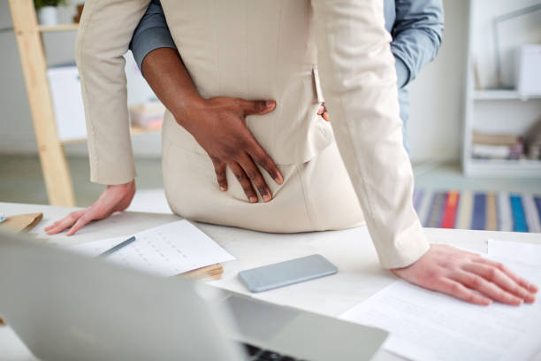 Close-up of unrecognizable black man stroking back of sexual partner while embracing her during sexual activity in office stock photo