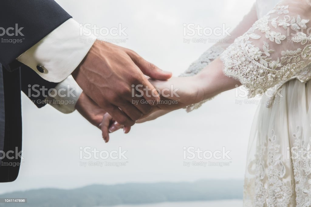 Closeup of unrecognizable bride and groom holding hands outdoors stock photo