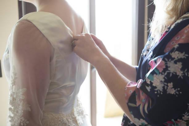 nahaufnahme von unkenntlich braut mutter zipping tochter kleid - mütterbrautkleider stock-fotos und bilder