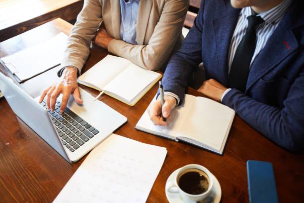 Nahaufnahme von unkenntlich Geschäftskollegen mit Laptop und Notizen im Tagebuch während der Diskussion Online-Daten zusammen, Business Analyse-Konzept – Foto