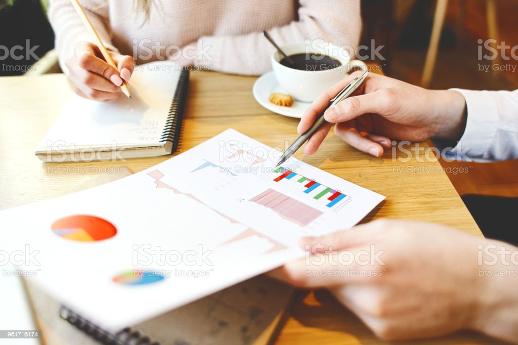 Close-up of unrecognizable business partners discussing graphs and charts in market research while planning business strategy royalty-free stock photo