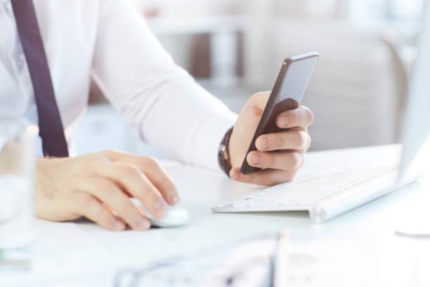 Nahaufnahme eines nicht wiederzuerkennenden Geschäftsmannes in formellem Hemd, der am Schreibtisch sitzt und während der Arbeit im Büro das Smartphone überprüft – Foto
