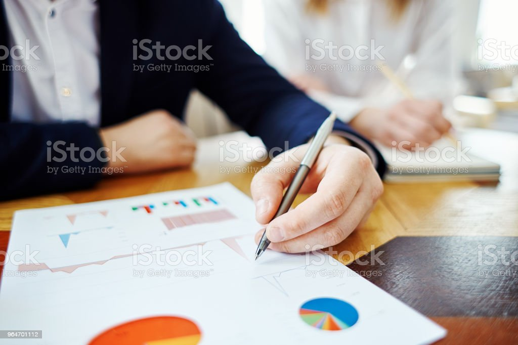 Closeup of unrecognizable businessman pointing at graphs with pen while analyzing financial report, his female colleague in the background royalty-free stock photo