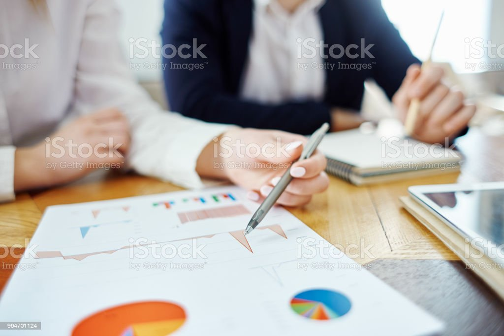 Closeup of unrecognizable businesswoman pointing at graphs in financial report with pen, her male business partner in the background royalty-free stock photo