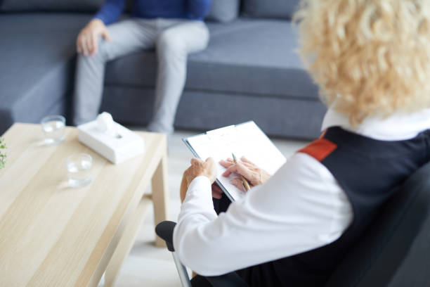Close-up of unrecognizable female professional psychiatrist sitting on chair and making important notes in clipboard while talking to patient at therapy session in office stock photo