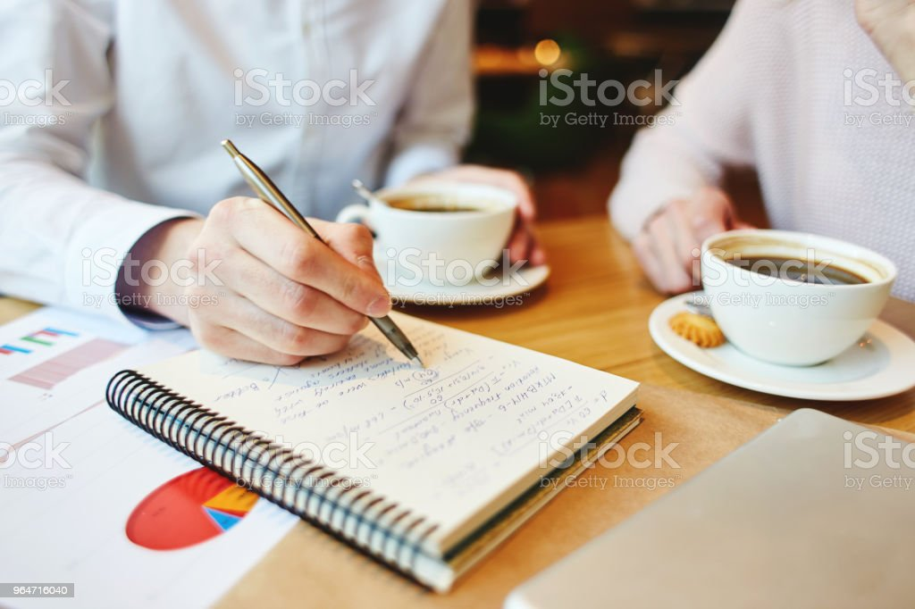 Close-up of unrecognizable man and woman having coffee at cafe and discussing assignment in notepad royalty-free stock photo