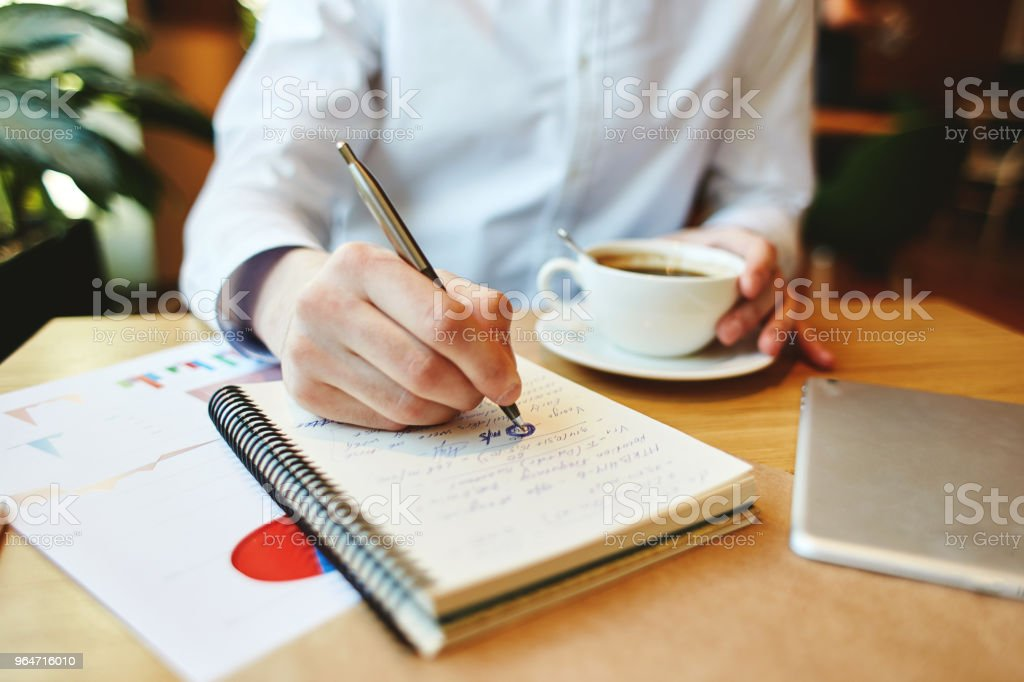 Close-up of unrecognizable man in white shirt having coffee while sitting at table and making calculations in notepad royalty-free stock photo