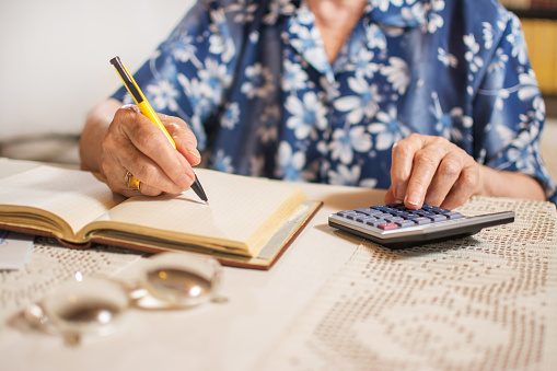 istock Close-up of unrecognizable senior woman doing finances at home. 603187300