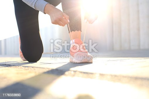 Closeup of unrecognizable sport woman tying sports shoes during evening run outdoors.