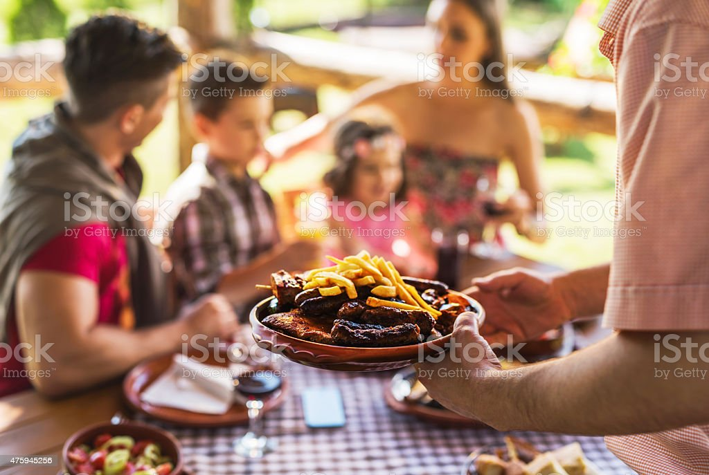 Close-up of unrecognizable waiter serving food to family in restaurant. stock photo