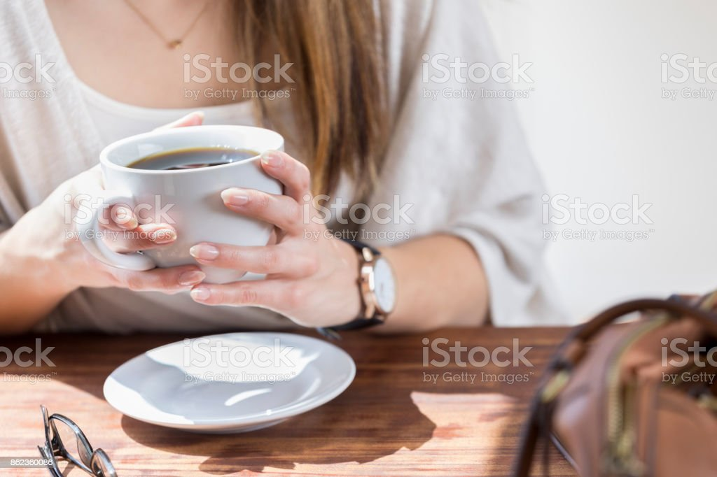 Closeup of unrecognizable woman holding coffee mug at table stock photo