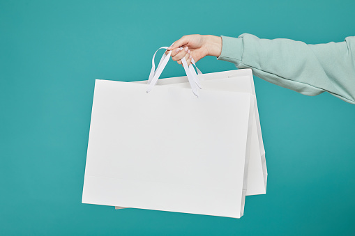 Close-up of unrecognizable woman in teal sweater holding white shopping bags against isolated background