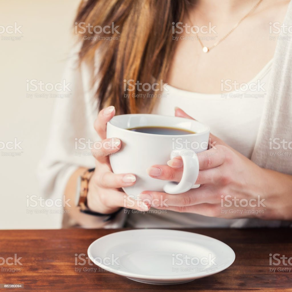 Closeup of unrecognizable woman warming hands on coffee mug stock photo