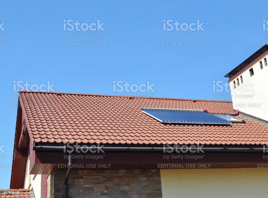 : Closeup of Vacuum Solar Water Heating System Rain Gutter on the Red Tiled House Roof. stock photo