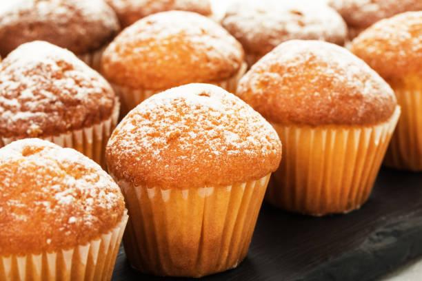 nahaufnahme der vanille muffins in puderzucker. selektiven fokus. - vanille muffins stock-fotos und bilder