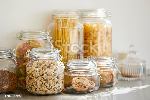 Close-up of various food in airtight jars. Groceries are seen through glass containers. Eatables are on table.