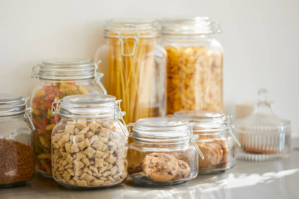 Close-up of various food in airtight jars Close-up of various food in airtight jars. Groceries are seen through glass containers. Eatables are on table. uncooked pasta stock pictures, royalty-free photos & images