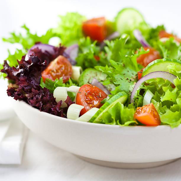 gros plan de salade de légumes sur fond blanc - saladier photos et images de collection
