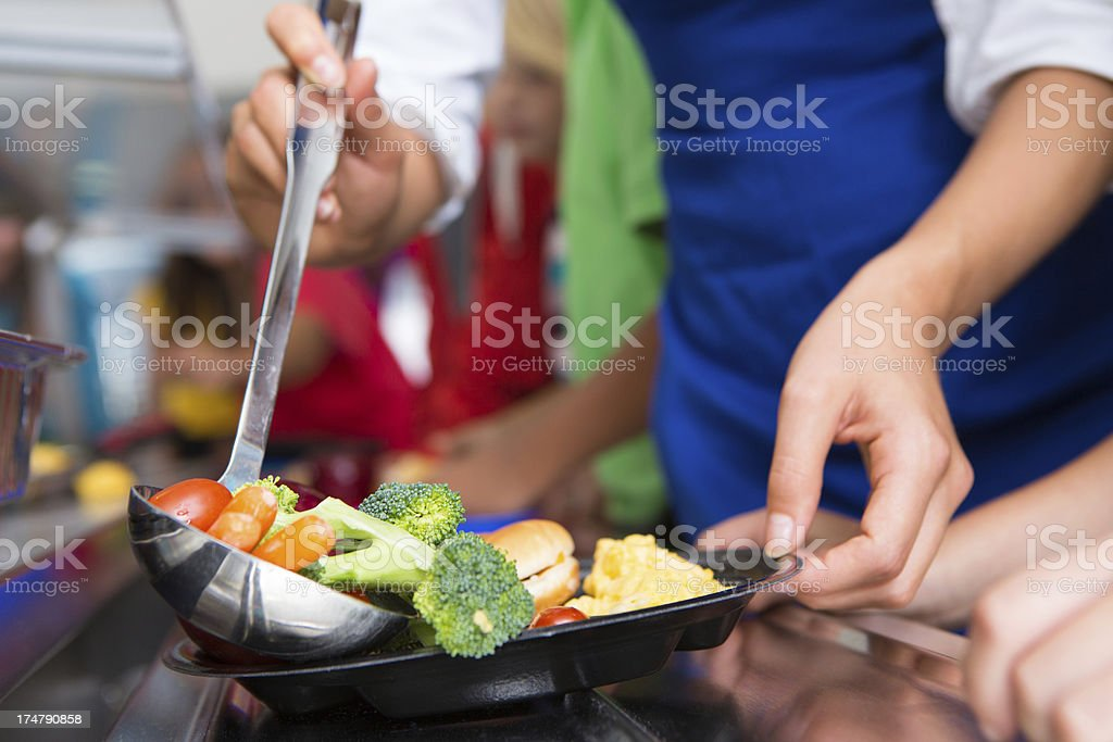 Closeup of vegetables being served in school lunch line stock photo