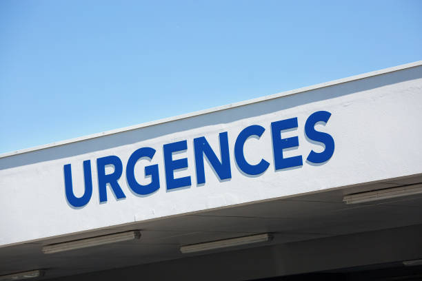 """Closeup of vertical red sign - """"Emergency"""" (""""Urgences"""" in French). stock photo"""
