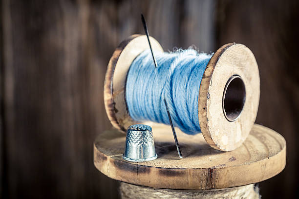 closeup of vintage needle and blue threads - sewing machine needle stock photos and pictures