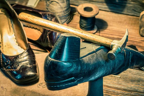 närbild på vintage skomakare arbetsplats med trasiga skor och verktyg - remmar godis bildbanksfoton och bilder