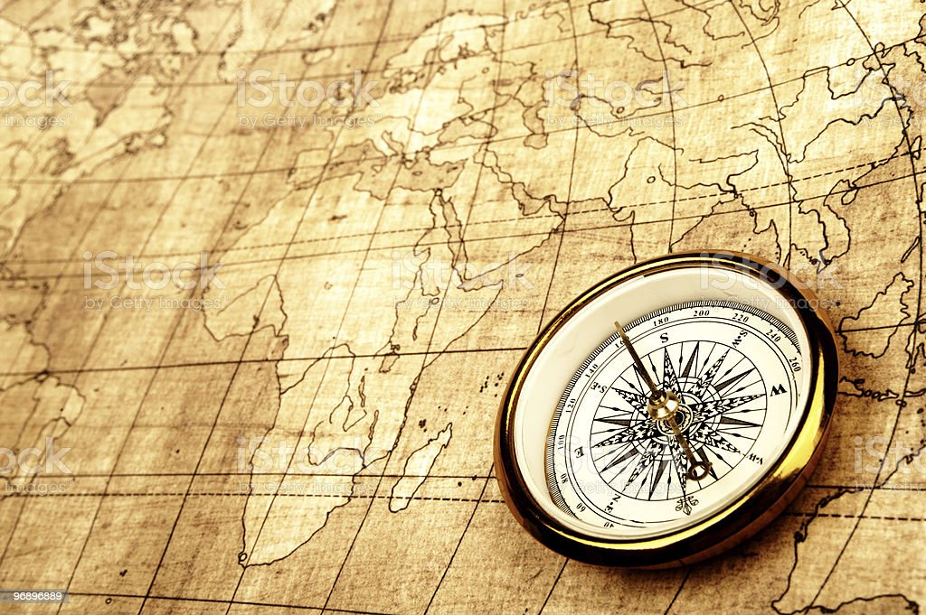 Close-up of vintage world map and compass royalty-free stock photo