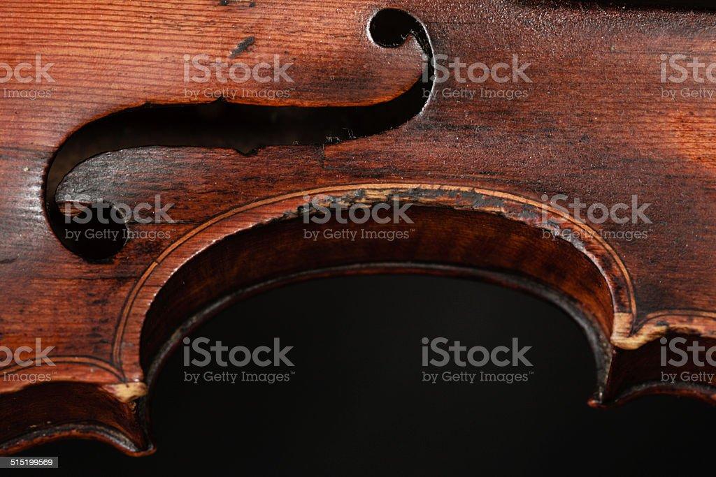 Art. Closeup of old wooden violin stringed instrument on dark gray....