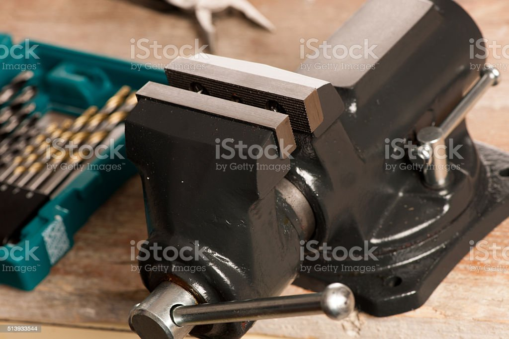 Closeup of vise tool clamping device on wooden background. stock photo