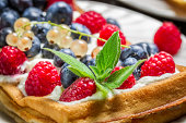 Closeup of waffels with cream and berry fruits.