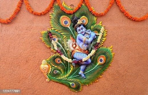 Indian Hindu God Little Krishna playing bansuri or wind blowing musical instrument